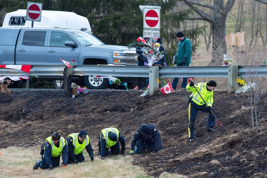 Royal Canadian Mounted Police investigators dig in the dirt on the roadside searching for evidence.