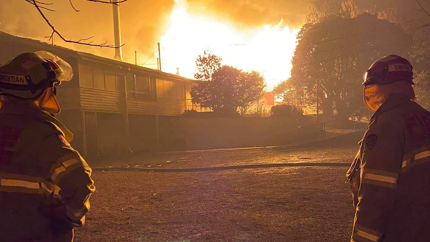 firefighters watching a building burn down