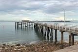 Mandorah jetty under grey clouds.