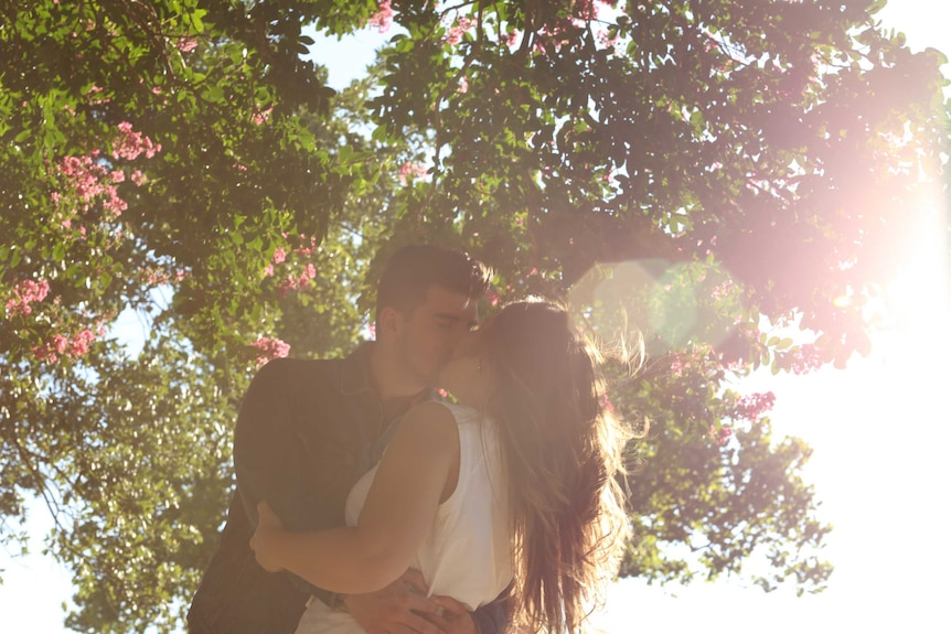 A young couple of high school sweethearts embrace and kiss under a tree dotted with pink flowers.