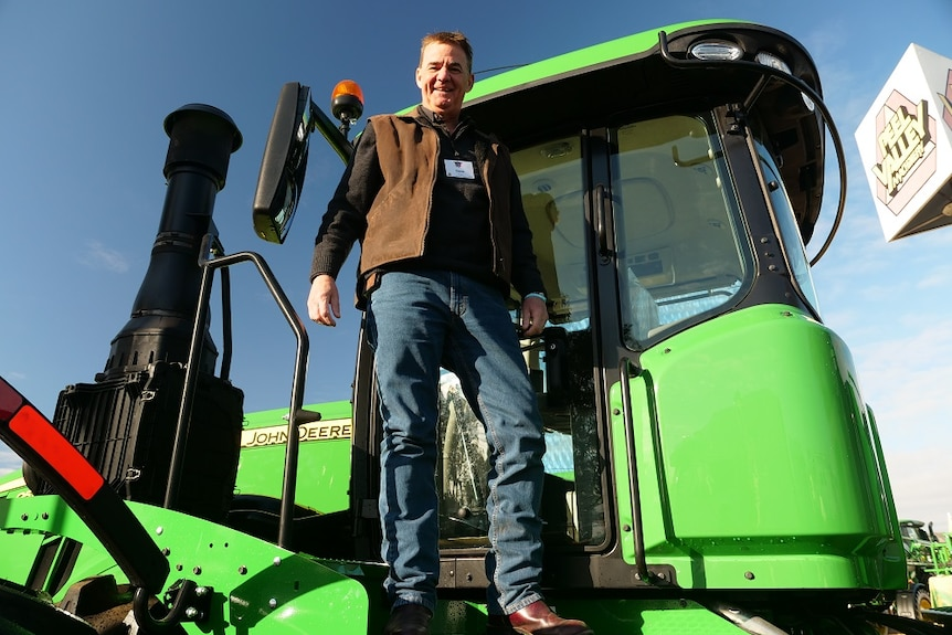 Steve John stands on the steps of a green tractor.