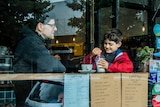 Outside a cafe looking through the window at a man and his son and other patrons