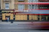 A time lapse photo of people walking past a boarded up pub while a double decker bus passes