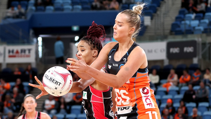 A Giants Super Netball player competes for the ball alongside an Adelaide Thunderbirds opponent.