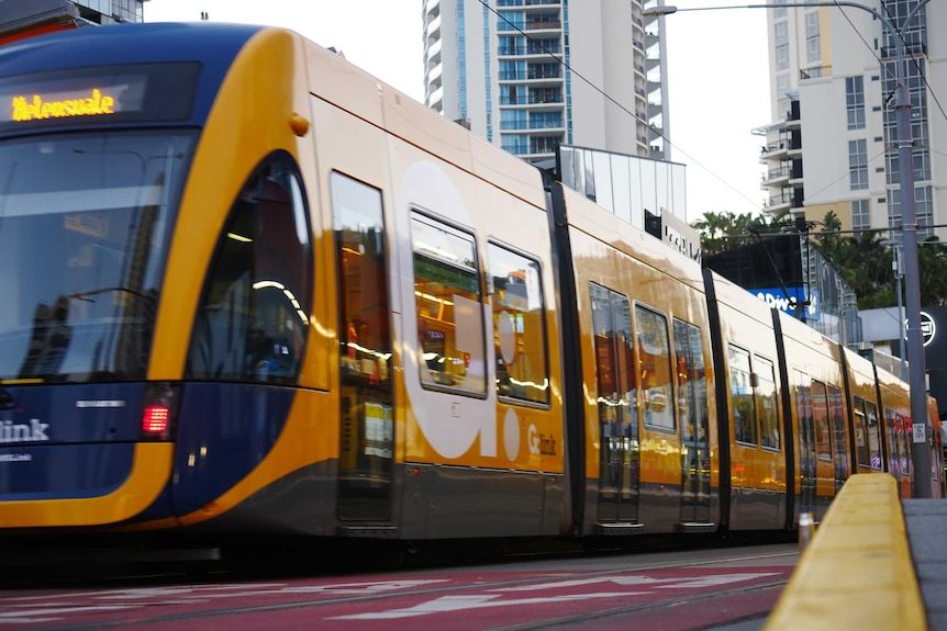 A yellow and blue light rail vehicle is stationary at a stop in Surfers Paradise. Tall buildings are in the distance