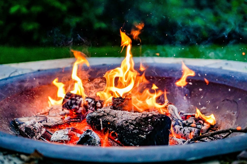 Wood burning in an outdoor fire pit.