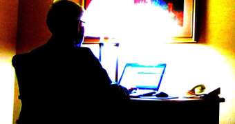 A man sits at a desk looking at a laptop.