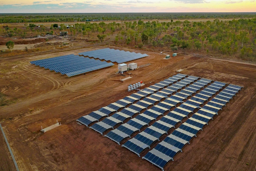 A drone shot of rows of shining solar panels on red dirt with a flat treed landscape behind.