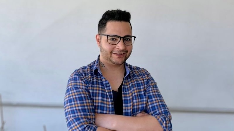 Karan wearing glasses and smiling with his arms crossed in front of him, in story about career change due to disabiilty.
