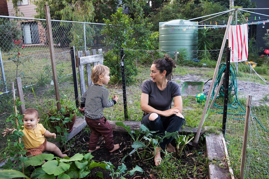Milenka sitting in the veggie patch in their backyard with her two young kids.