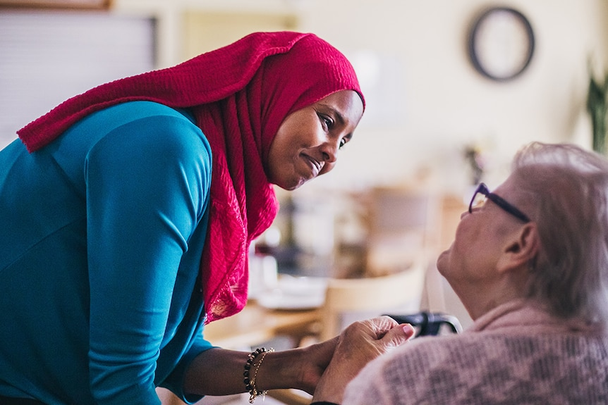 A woman wearing a headscarf holding the hand of an elderly woman.
