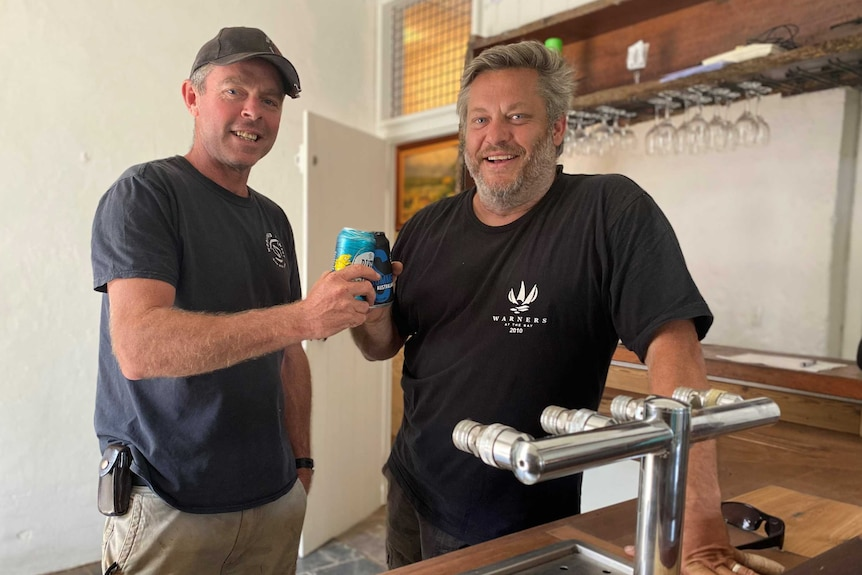 Two men stand behind a bar and cheers