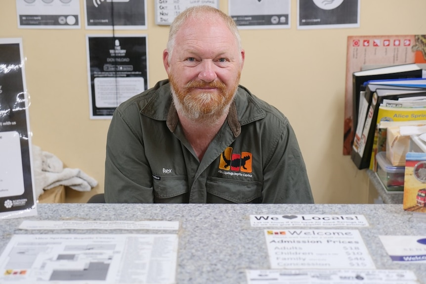 Rex Neindorf sits at a desk at the Alice Springs Reptile Centre.