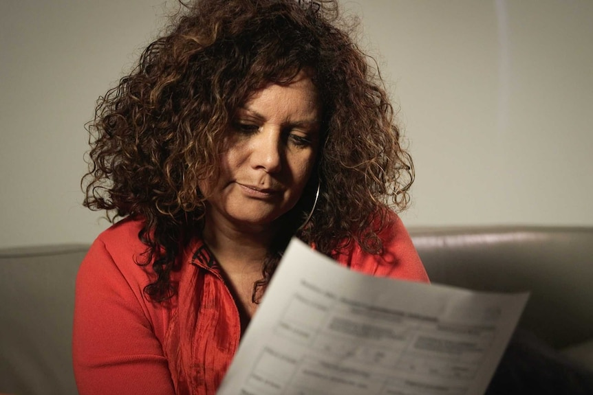 Malarndirri McCarthy purses her lips while looking at a piece of paper.