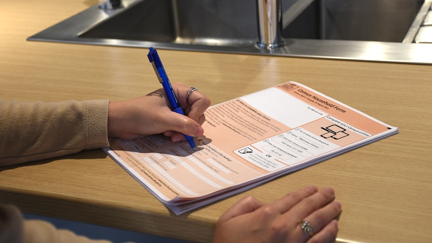 A hand holds a pen to an orange Australian census form.