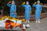 Three people in full PPE salute behind two stretchers carrying bodies wrapped in fabric.