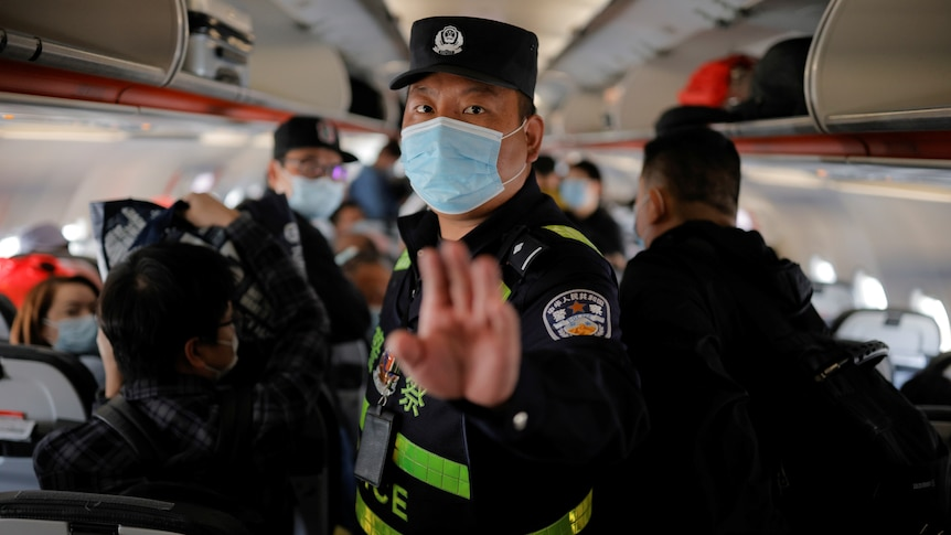 A Chinese police officer puts his hand up to order journalists off a plane in Xinjiang, China.