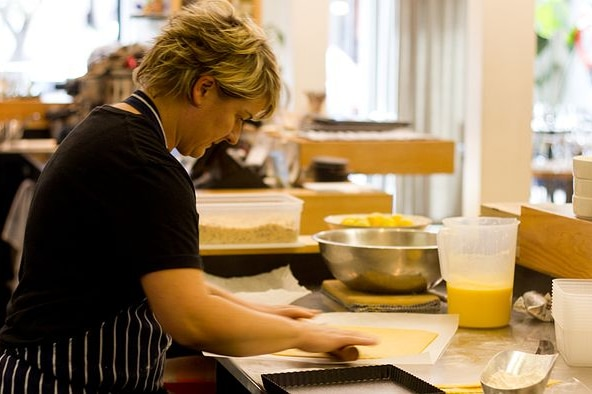 A chef leans over a commercial kitchen table, using a rolling pin to flatten out a pastry to turn into a lemon tart.