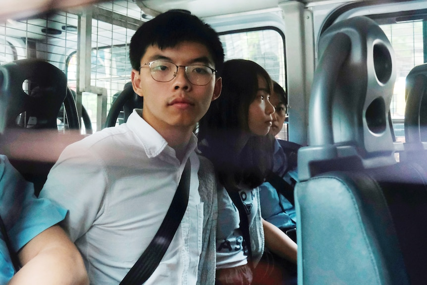 You see the back seat of a white police van carrying three young Hongkongers handcuffed with Joshua Wong at their centre.