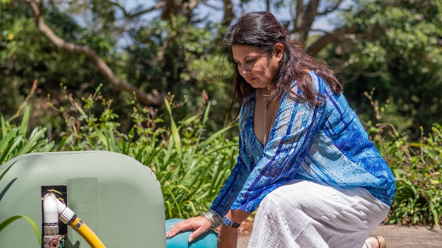 A woman in a blue shirt and long white dress kneels before a water pump, with a concerned look on her face.