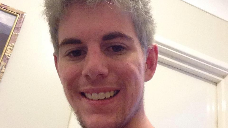a selfie of a man smiling and looking down at the camera in front of a cream wall