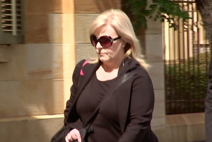 A blonde woman wearing sunglasses outside a sandstone building
