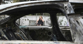 A woman looks on amid burned cars in Mati, Greece after a fire.