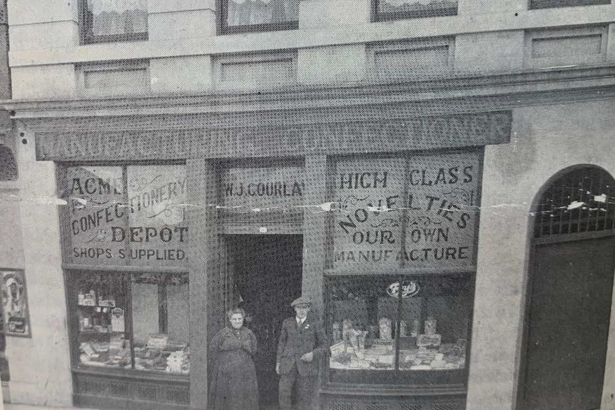 Photo en noir et blanc d'une ancienne pâtisserie avec deux personnes debout à l'entrée.