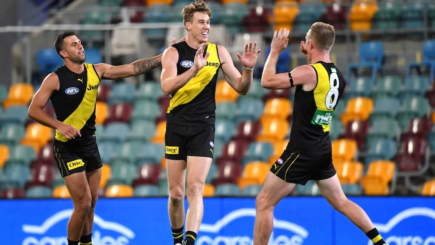 Two AFL teammates move to high five after a goal for their side.