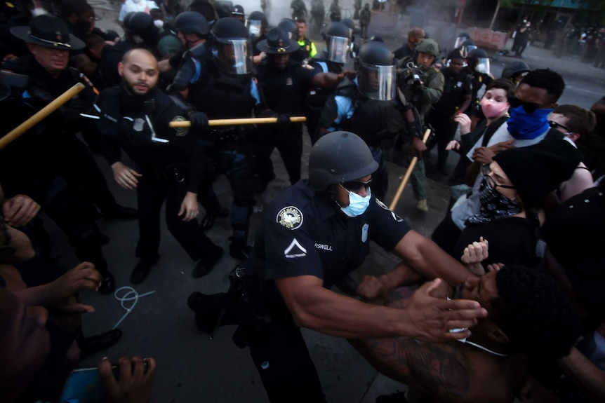 About 50 people, a mix of police and protesters, clash in a street, with a black police officer putting his hands on a black man