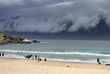 People go about their day on Bondi Beach in Sydney as a storm front moves towards the city.