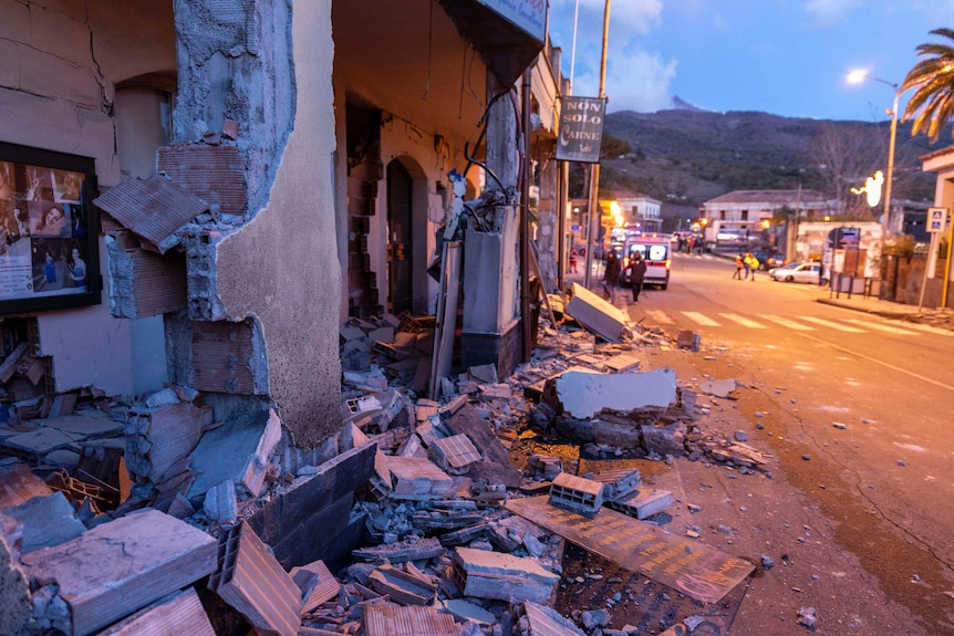 The front facade of a house on a narrow Italian street lies partially destroyed with debris strewn across the road.