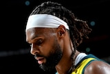 An Australian male basketballer looks towards the floor during a game at the Tokyo Olympics.