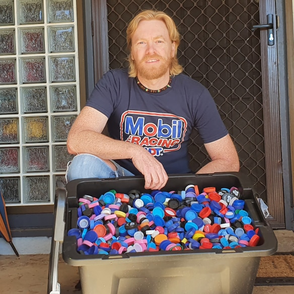 A man with red hair and a red beard kneels behind a large container of plastic lids.