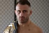 Alex Volkanovski stands shirtless with a belt over his shoulder inside a fighting gym.