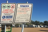 Camping permitted signs in foreground with caravans and mobile homes in background