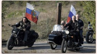 Russian President Vladimir Putin riding a motorcycle among a group of riders showing off Russian flags.