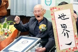 Chitetsu Watanabe smiles with his first raised in celebration as his hold this Guinness World Record certificate.