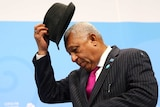 Frank Bainimarama takes off his hat.