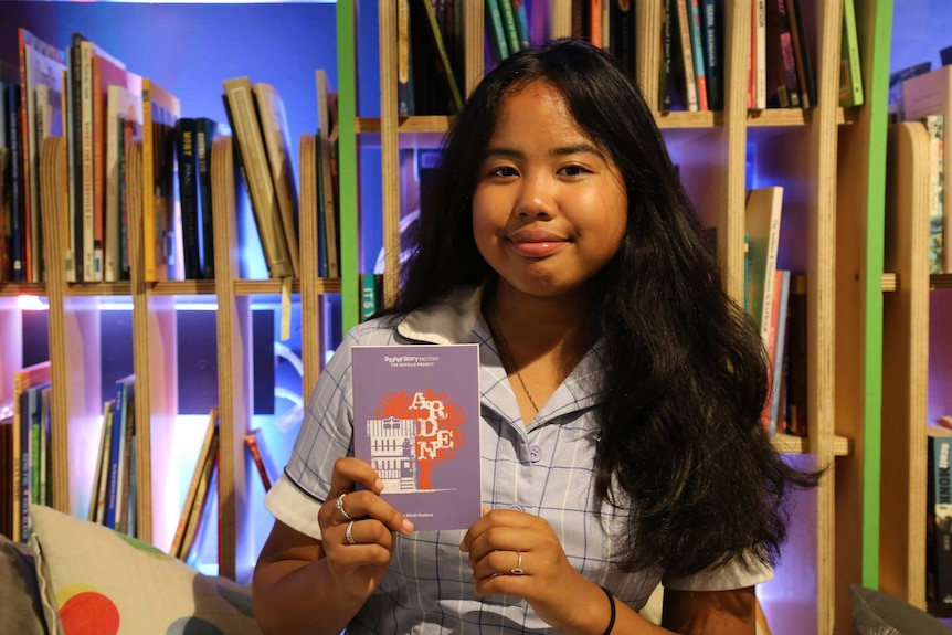 A girl holds a book