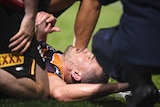 Corey Oates lies on the ground eyes closed as people kneel around him.
