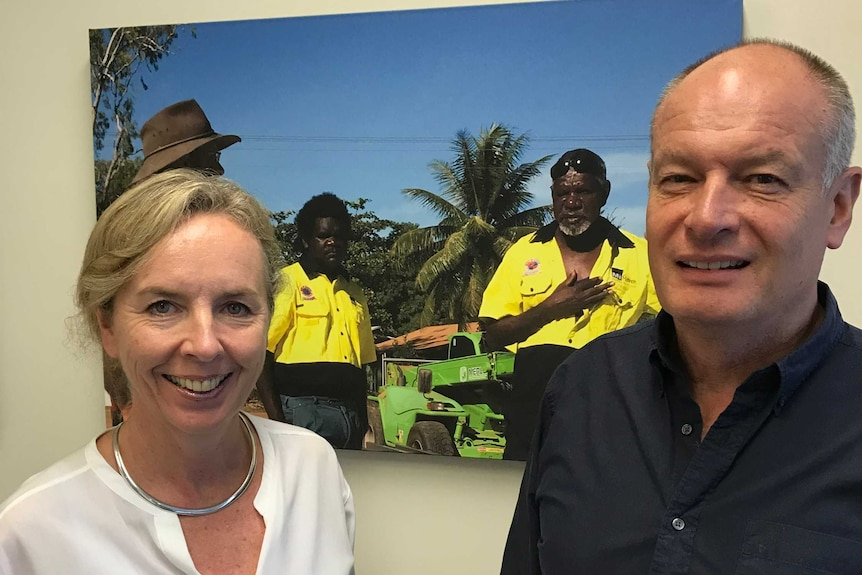 A woman in a white shirt and a man in a black shirt standing in front of a photo of two employees.