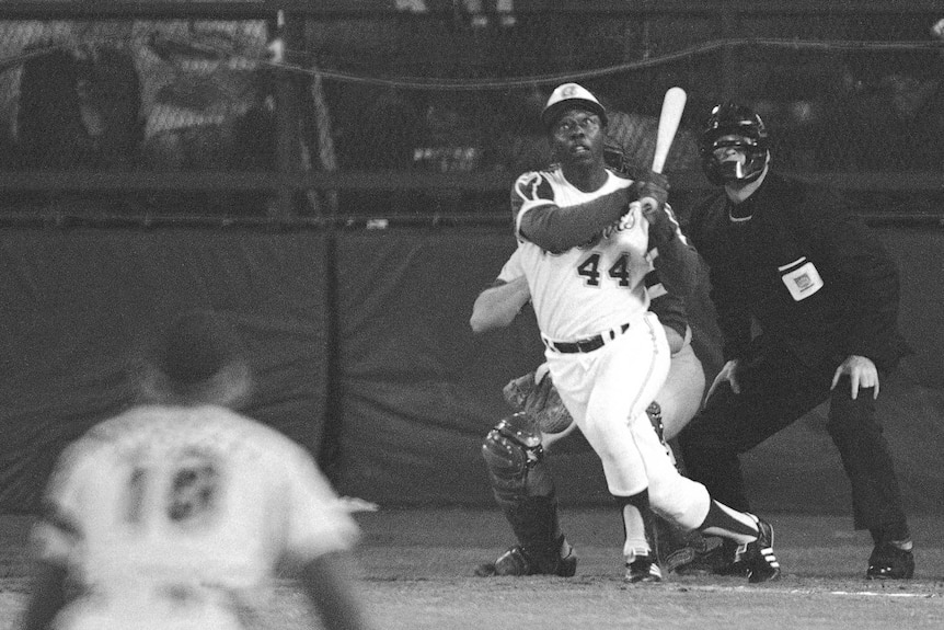 Hank Aaron watches the flight of a ball as he hits a home run for the Atlanta Braves against the LA Dodgers in 1974.