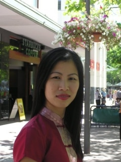 A woman in a red outfit looking at the camera.