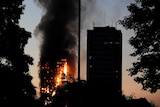 A dusk shot shows a burning building tower in the background as another high rise is in shadows in the foreground.