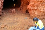 An Aboriginal man in jeans and a hi-vis shirt sits at the entrance to a cave with another man standing in the mouth of the cave.
