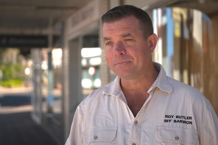 Roy Butler wearing a white shirt standing outside a shopfront.