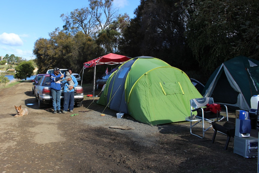 Homeless men stand next to their tents