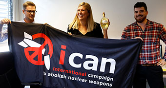 International Campaign to Abolish Nuclear Weapons members hold banner.