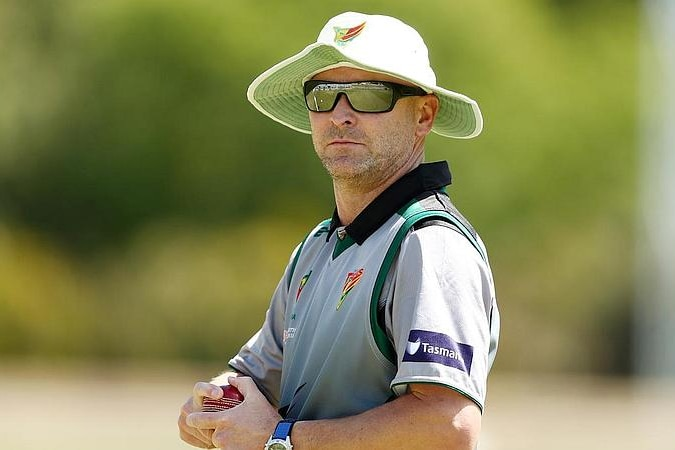 A man wearing sunglasses and a white wide-brimmed hat holds a cricket ball with both hands.